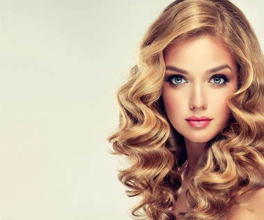 Beautiful girl blonde hair with an elegant hairstyle , hair wave ,curly hairstyle . Jewellery , earrings and bracelet